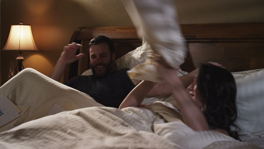 Couple in bed. man works on laptop and wakes woman. they have a pillow fight.  | Shutterstock HD Video #2062886