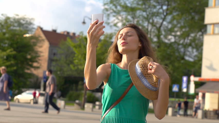 Girl chatting on cellphone and showing town to someone, steadycam shot, slow motion shot  | Shutterstock HD Video #20638504