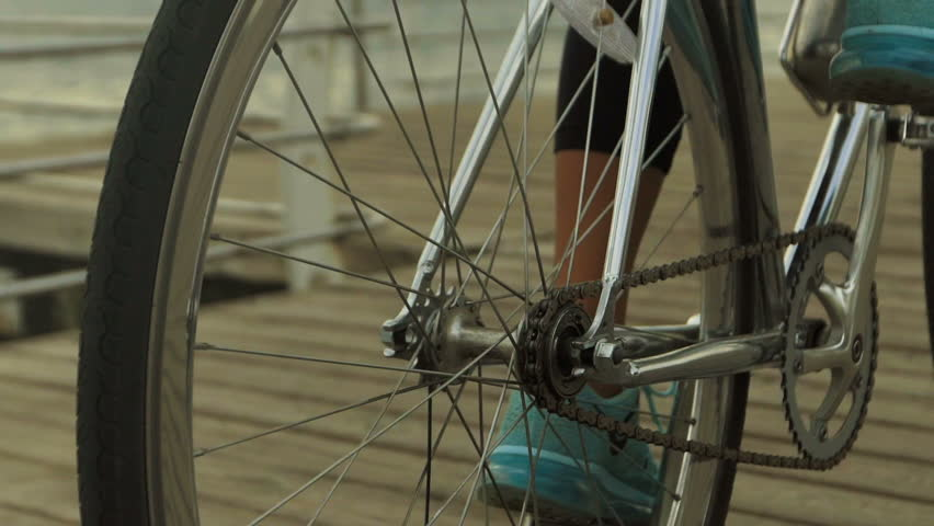 Close up of woman wearing blue gym-shoes, while riding her bycicle near the sea.