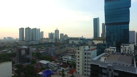 Panned view to the right of Jakarta business district, with various bank HQ and luxury hotels, during sunset around Bundaran Hotel Indonesia along Sudirman avenue in Indonesia capital city.