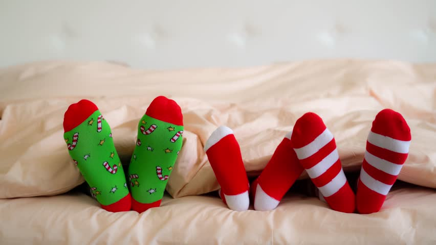 Family in Christmas socks in bed. Mother; father and baby having fun together. People relaxing at home. Winter holiday Xmas and New Year concept   Shutterstock HD Video #20661826