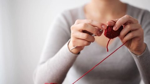 people and needlework concept - woman knitting with crochet hook and red yarn