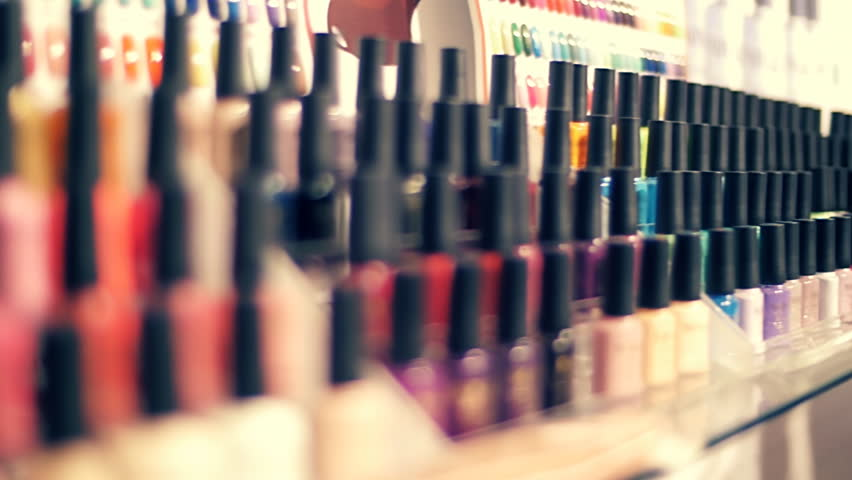 Rows of colorful bottles of nail polish on the showcase of store. Closeup. Dolly shot. Shallow depth of field