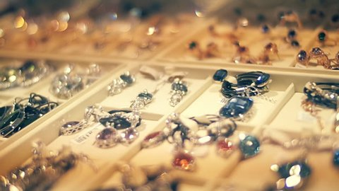Beautiful jewelry on store shelves shimmer in different colors in rays of light. Closeup. Shallow depth of field