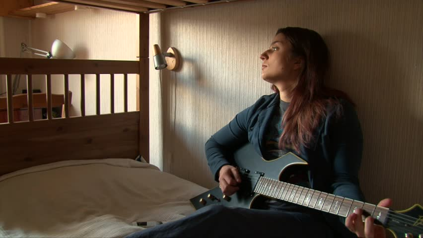 Girl Playing Guitar At Home On Bunk Bed
