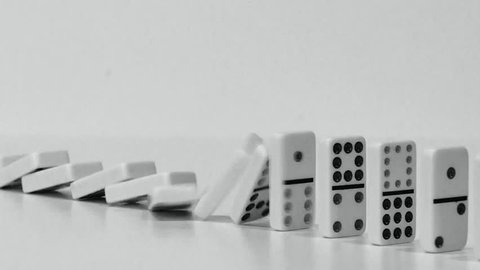 DOMINO EFFECT - white dominoes fall in chain reaction B/W with plenty room for copy Fade in & fade out to white Pan L-R