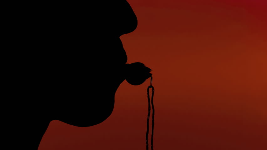 Silhouette shot of a woman blowing into a whistle. Red background.