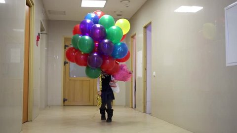 Little girl is going on the corridor and holding in hands many balloons with bunch of flowers.