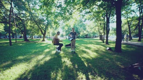 Music band. Duet. Ensemble. Singer and performer. Song's author. Singer and musician. Two men play a guitar outdoors in summer park. One of the musicians singing into the microphone. Two guitars.