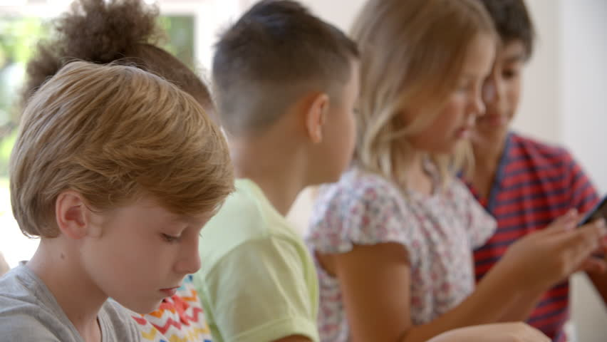 Group Of Children Sit On Window Seat And Use Technology  #20711176