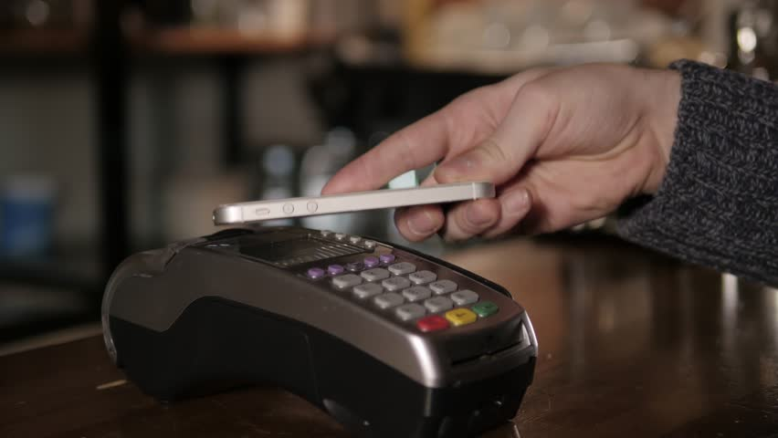 Customer paying with NFC technology by mobile phone on terminal in modern cafe