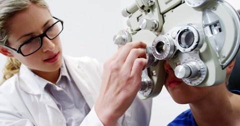 Caucasian female optometrist examining young patient on chiropter in ophthalmology clinic