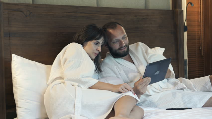 Young couple in bathrobes watching movie on tablet lying on bed at home    HD stock. Couple Looking On Something On Modern Laptop And Smartphone In The