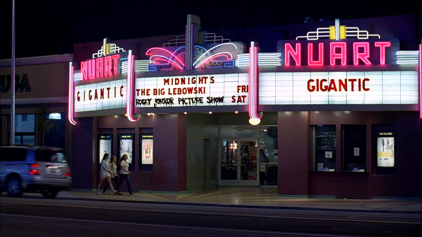 night Static Raked right small town Nuart theate right, playhouse independant movie small concert venue, neon lights Gigantic other movies listed marquee 3 women enter