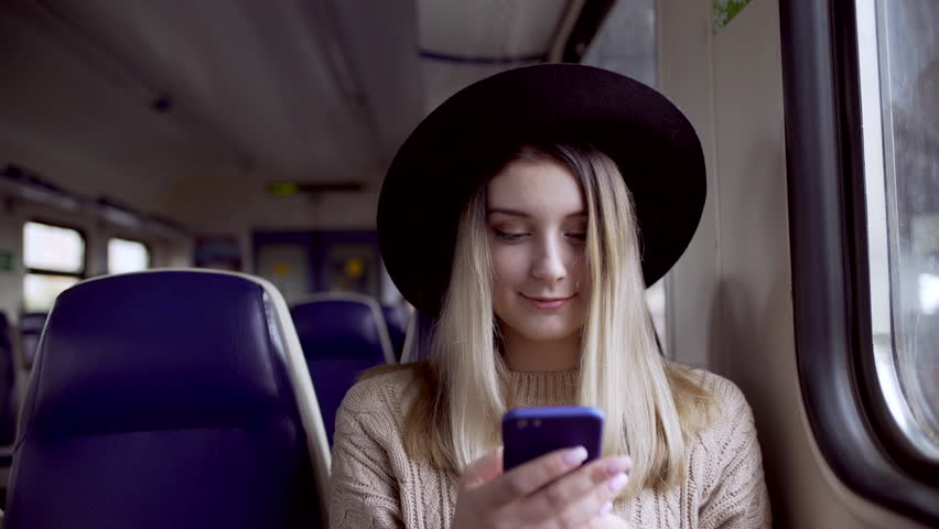 Close up shot of young woman wearing broad brim, typing message on her phone sitting in suburban electric train | Shutterstock HD Video #20755126
