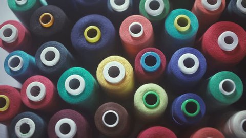 Manufacture industrial textile spinning. Textiles and Fabrics. Shot of colorful rolls of woolen. Needlework, sewing and tailoring concept - row of colorful thread spools on table. Spools of thread.