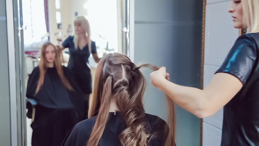 Hair stylist makes professional hairstyle of young woman in beauty studio using curling irons   Shutterstock HD Video #20760256