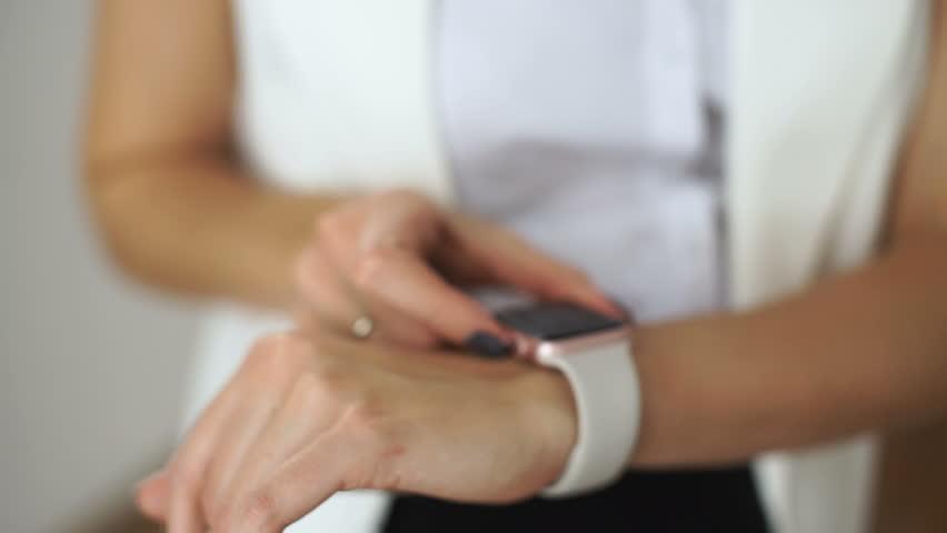 Smartwatch. Young woman using smart watch in cafe. Closeup of female touching touch screen on watch entering watch app. | Shutterstock HD Video #20789083