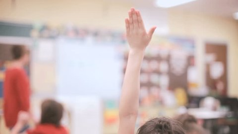 Student raising hand in elementary school classroom