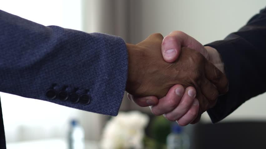 We see a handshake between two businessmen. The agreement between them had been reached. One of them is an African American/Handshake of Two Businessman - is the Completion of the Transaction | Shutterstock HD Video #20801821