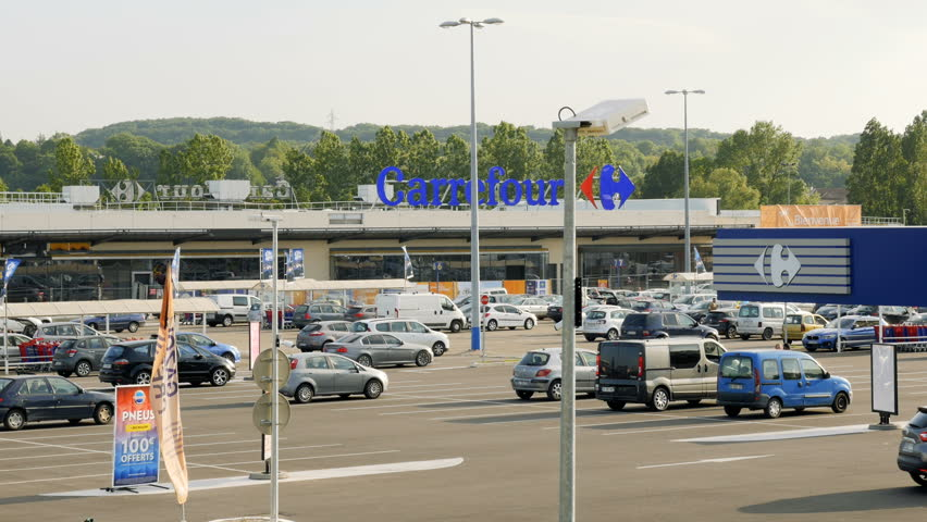 PARIS, FRANCE - CIRCa 2016: Hypermall Carrefour S.A. facade in with customers exiting store and loading groceries in the large parking. It is one of the largest hypermarket chains in the world