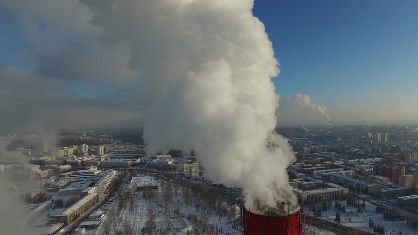 White smoke from the chimney of thermal power station boiler room, thermal power plant, aerial survey, white smoke against a blue sky, very cold