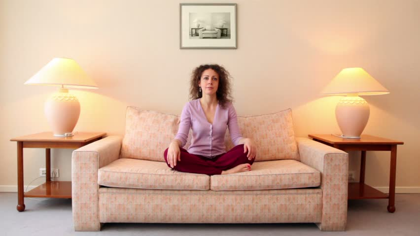 Woman sits on sofa in lotos pose, then closes her eyes and meditates