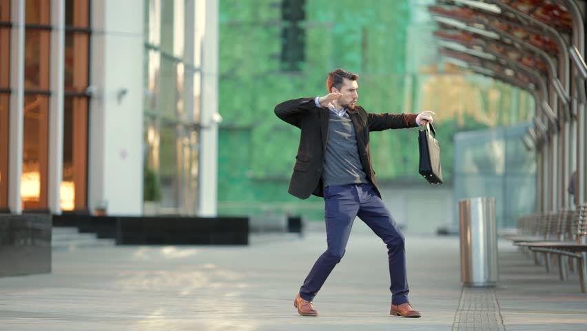 Attractive man with a beard and briefcase dancing in the street | Shutterstock HD Video #20821489