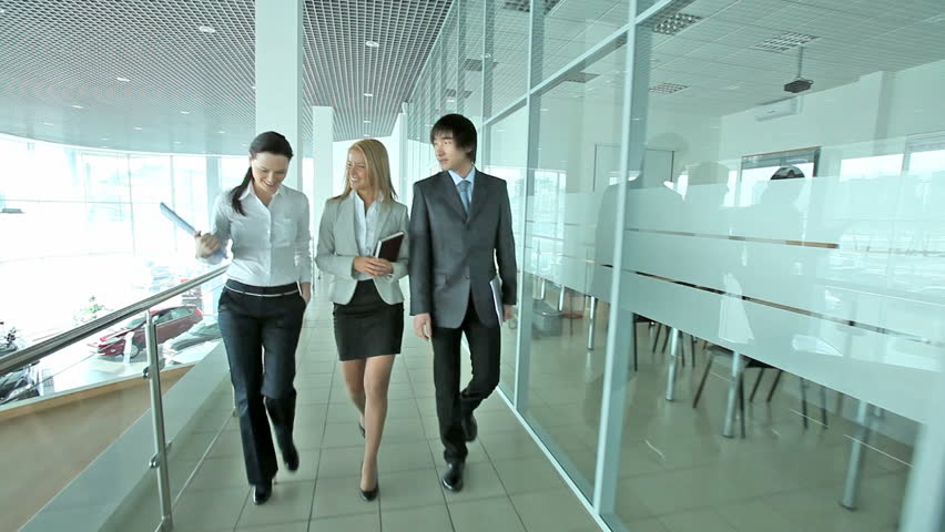 Cheerful business people walking together along the office corridor and holding a conversation, dolly shot