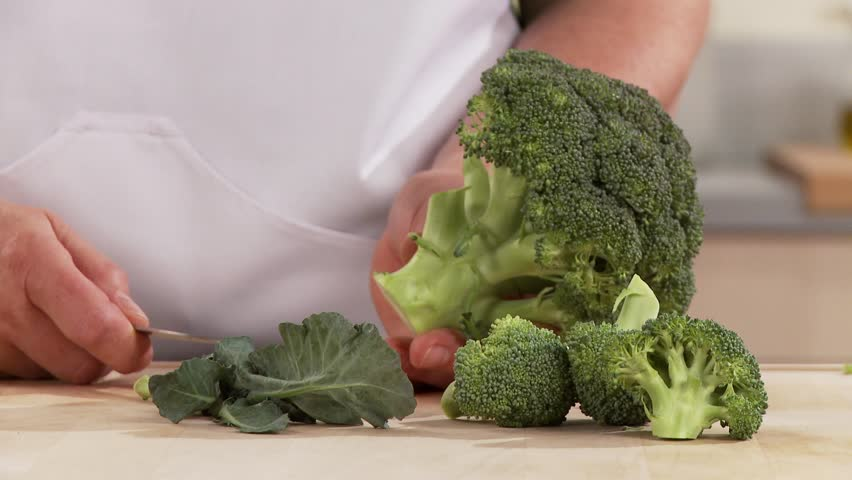 Broccoli being broken into florets