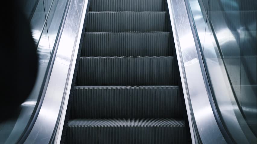 Close-up shot of young man with bag moving on escalator,  traveling on train. Rush hour, subway underground station. Modern escalator stairs moving up.