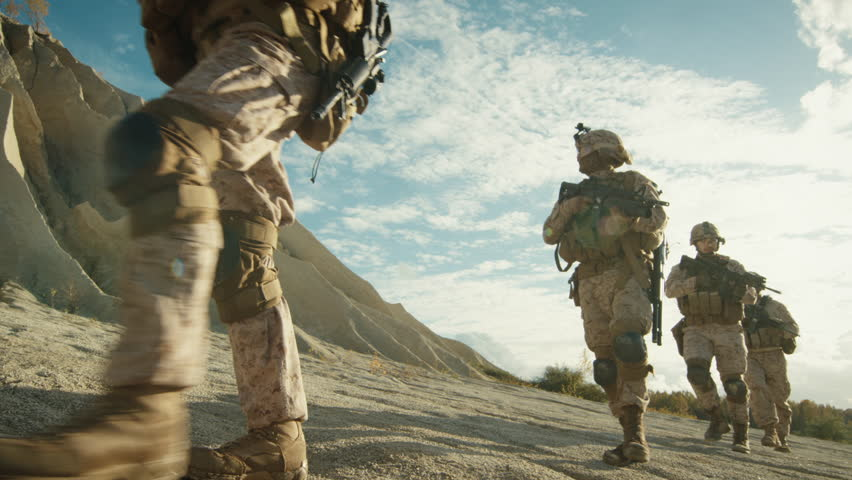 Squad of Fully Equipped and Armed Soldiers Walking in Single File in the Desert. Slow Motion. Shot on RED EPIC Cinema Camera in 4K (UHD).