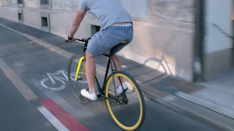 Young hipster man in casual summer cloths riding his fixed gear bike along the bike lane on city street