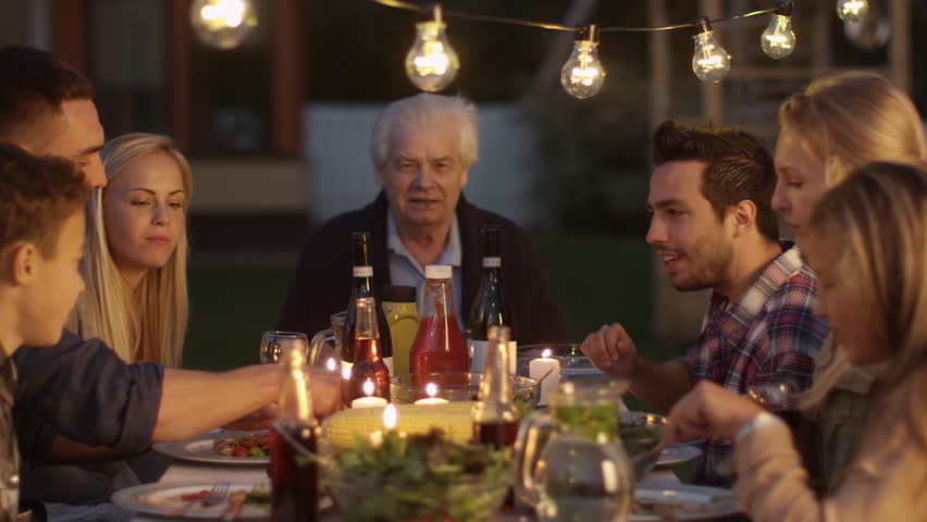 Group of People Sitting Around a Table, Eating, Communicating and Having Fun during Family Dinner. Shot on RED Cinema Camera in 4K (UHD). | Shutterstock HD Video #20914216