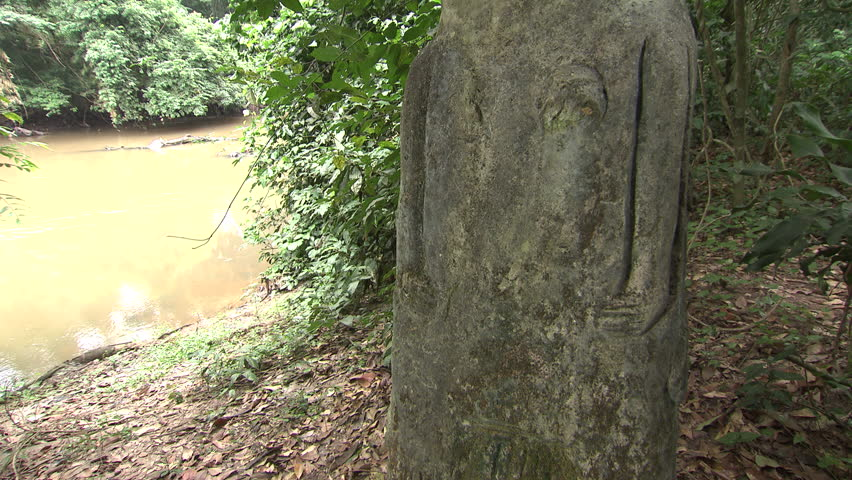 Osogbo, Nigeria - August 2013; Tilt up carved statue in Sacred Grove, Osun River in background.