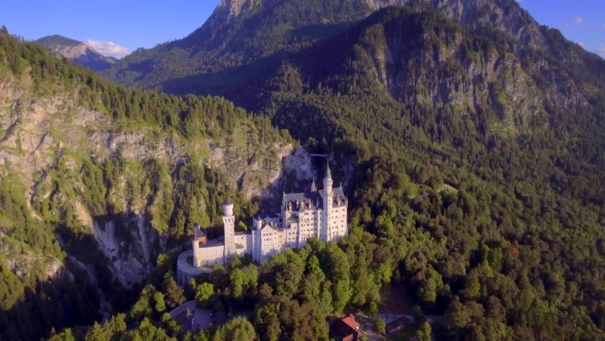 Romantic fairytale disneyland inspiration Neuschwanstein castle mountain forest landscape horizon sunny day Germany aerial rotating motion