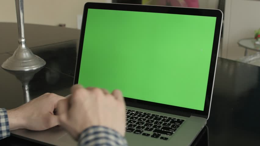 Poland, Lublin - May 02, 2016: A man types on a laptop on his desk. Green screen for your custom screen content.