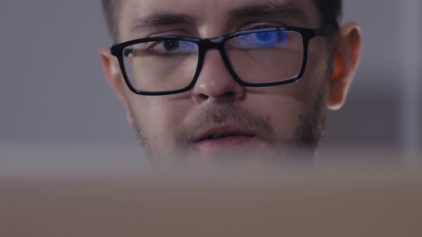 Man in black rim glasses using his computer in office. Businessman with Screen reflection in the lens | Shutterstock HD Video #20934886