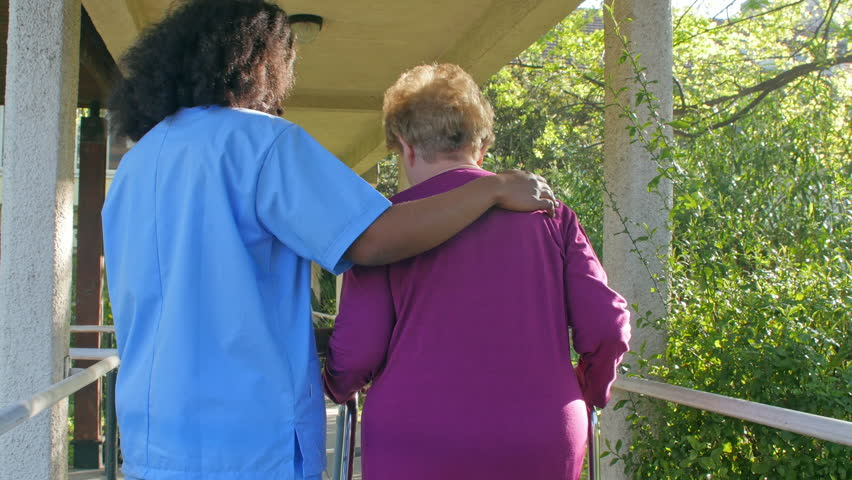 Nurse helping woman with crutches outdoor. Rehab concept.