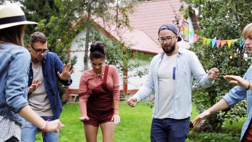 Leisure, holidays, fun and people concept - happy friends dancing at summer party in garden | Shutterstock HD Video #20971636