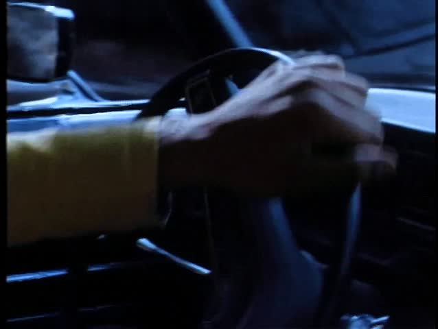 Close-up of person turning steering wheel in car