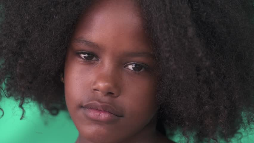 Portrait of Cuban children with emotions and feelings. Black young girl from Cuba looking at camera with worried face, child with sad expression. Close-up. Real green wall on background, no chroma key