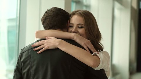 couple meeting at the airport. boyfriend hugging his girlfriend. real emotion