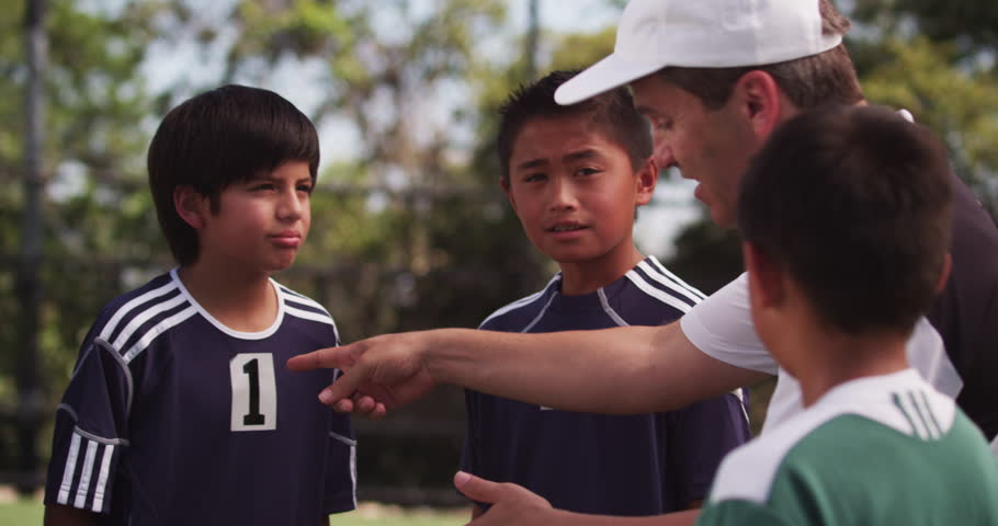 An enthusiastic coach gives his diverse team of youth league players a pep talk before sending them out onto the field.