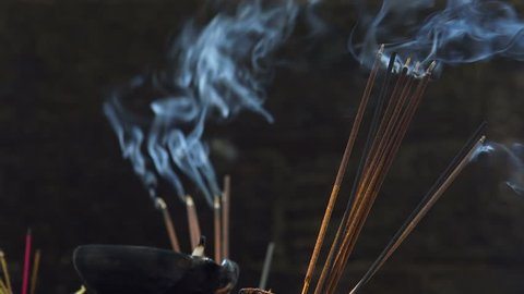 Burning incense joss sticks at temple. Traditional offering in buddhist and hindu temples