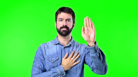 Handsome man making an oath on green screen chroma key