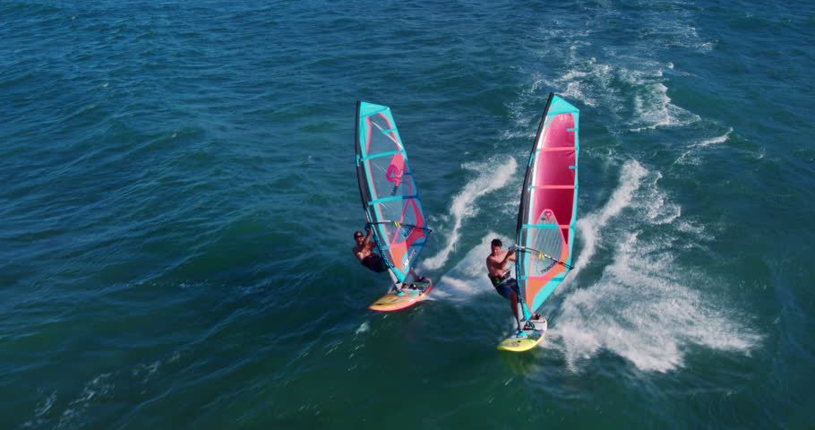 Aerial view of windsurfers gliding across blue ocean, extreme sport