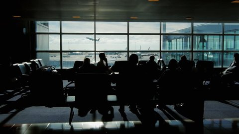 People are waiting for the flight in the airport terminal on a sunny day. Outside the window, the plane takes off. One can see the silhouettes of people, no recognizable faces