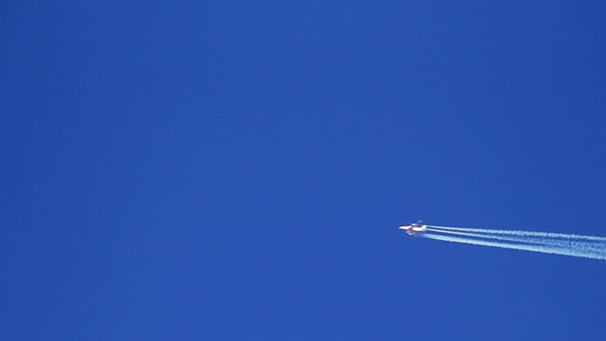 Airplane vapour trails across clear blue sky (slow motion)