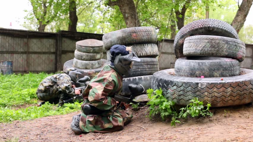 Two boys paintball players sit in ambush behind pile of tires